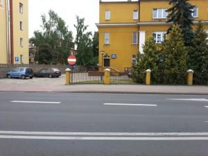 Za drzewami widoczny przód radiowozu sierżanta Toty