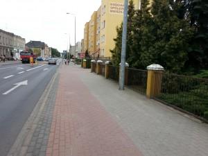 Ulica Surzyńskiego. Po prawej stronie - za drzewami wejście do Komendy i zaparkowany radiowóz sierżanta Toty